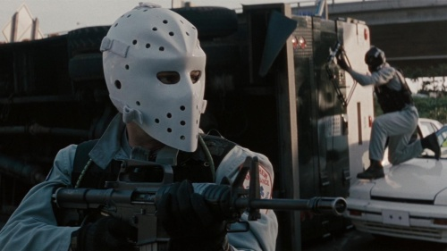 Heat opens with a botched heist, but it unlike every other crime picture that came out in the five years after Pulp Fiction, it's not a black comedy. I think that's Val Kilmer under the hockey mask.
